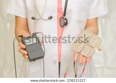 Doctor's hold Medical Tens Unit for pain therapy - stock photo