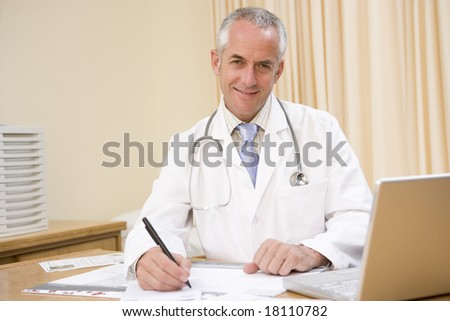 doctor sat at office desk smiling - stock photo