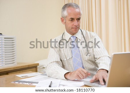 doctor sat at office desk working - stock photo