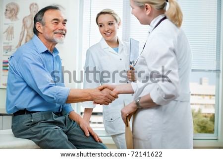 doctor shakes hands with a senior patient - stock photo