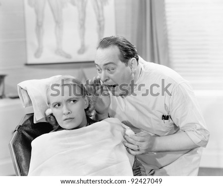 Doctor shouting into the ear of a patient - stock photo