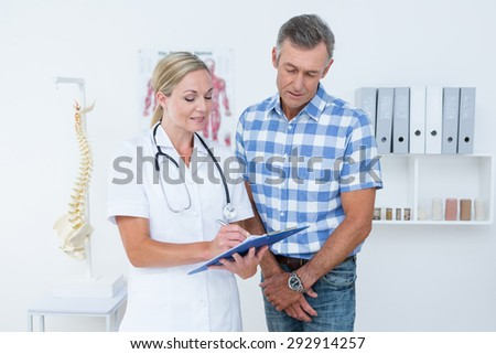 Doctor showing clipboard to her patient in medical office - stock photo