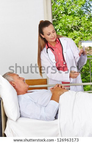 Doctor showing patient x-ray image at hospital bed - stock photo
