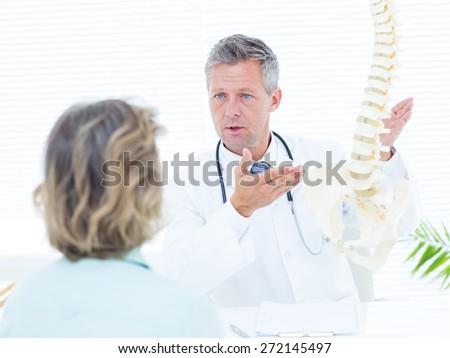 Doctor showing spine model to his patient in medical office - stock photo