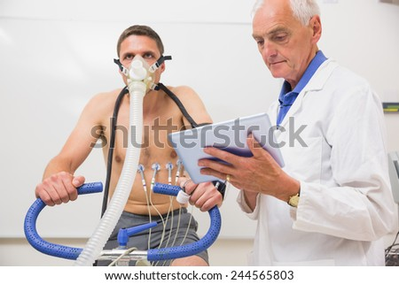 Doctor showing tablet pc to man doing fitness test at the medical centre - stock photo