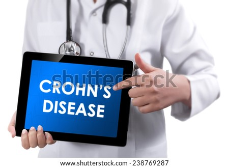 Doctor showing tablet with CROHNS DISEASE text.  - stock photo
