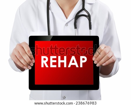 Doctor showing tablet with REHAP text.  - stock photo
