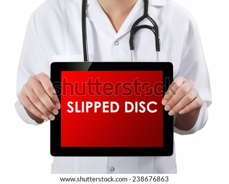 Doctor showing tablet with SLIPPED DISC text.  - stock photo
