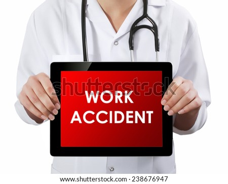 Doctor showing tablet with WORK ACCIDENT text.  - stock photo