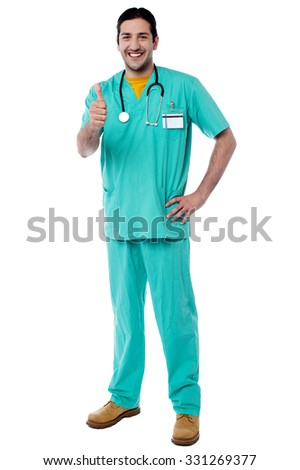 Doctor showing thumbs up gesture, full length shot. - stock photo