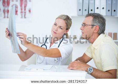 Doctor showing X rays to her patient in medical office - stock photo
