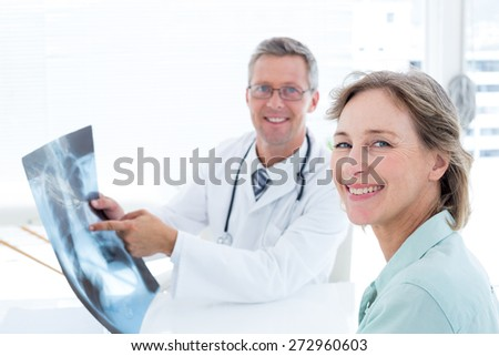 Doctor showing xray to his patient in medical office - stock photo