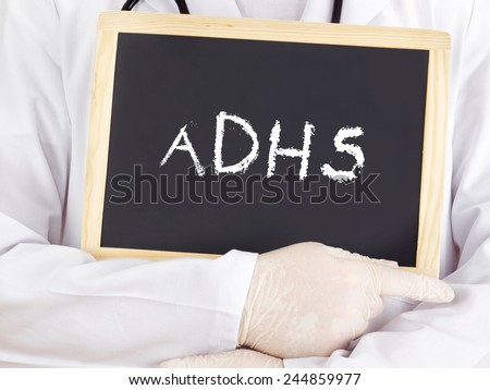 Doctor shows information on blackboard: adhs - stock photo