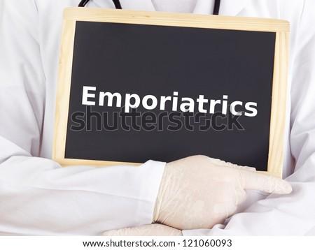 Doctor shows information on blackboard: emporiatrics - stock photo