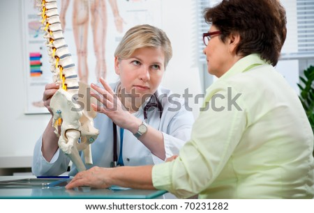 Doctor shows the problem areas on the spine's model to patient - stock photo