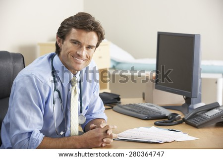 Doctor sitting at desk - stock photo