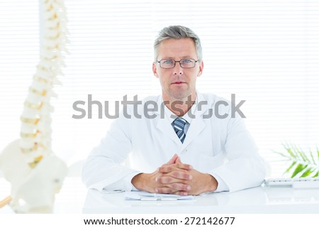 Doctor sitting at his desk looking at camera in medical office - stock photo