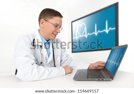 Doctor sitting at his desk with laptop computer. Heart beat - stock photo