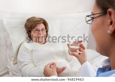 Doctor sitting in bed, gives medication and a glass of water to recovering senior patient - stock photo