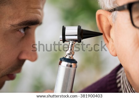 Doctor specialist Performs an Ear Examination close up - stock photo
