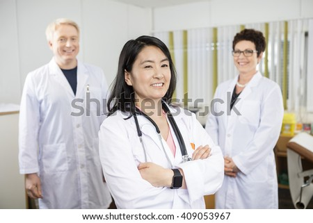 Doctor Standing Arms Crossed While Coworkers Smiling In Clinic - stock photo