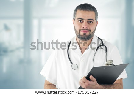Doctor Standing At The Hospital holding a Clipboard  - stock photo