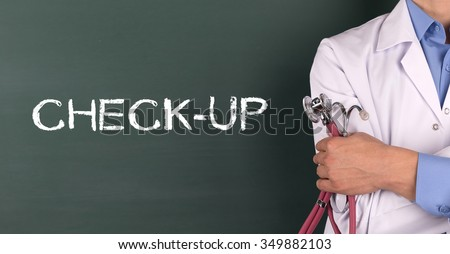 Doctor Standing front of Blackboard written CHECK-UP - stock photo