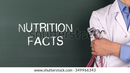 Doctor Standing front of Blackboard written NUTRITION FACTS - stock photo