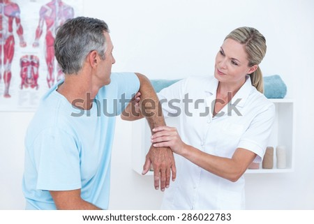 Doctor stretching a man arm in medical office - stock photo