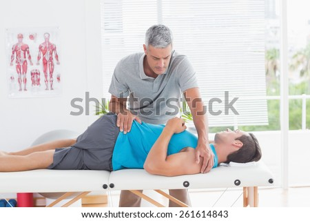 Doctor stretching a young man back in medical office - stock photo