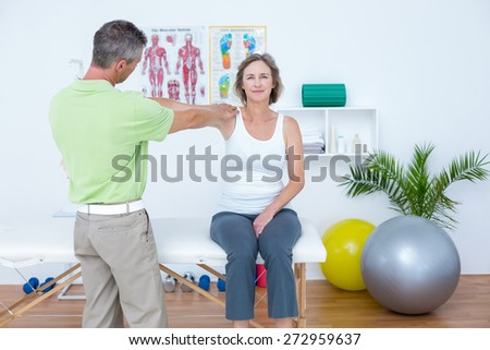 Doctor stretching his patients arm in medical office - stock photo