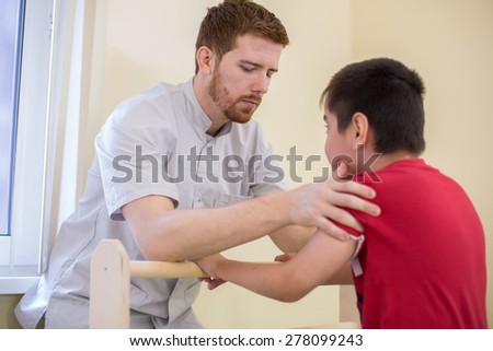 Doctor supports the child during physiotherapy treatment - stock photo