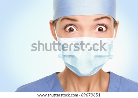 Doctor / surgeon shocked - funny. Woman closeup portrait of young doctor, surgeon or nurse surprised starring with big eyes wearing surgical mask. Asian / Caucasian female model. - stock photo