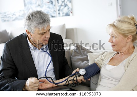 Doctor taking blood pressure to patient at home - stock photo