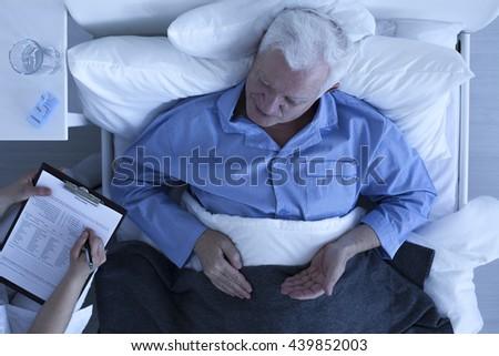 Doctor taking notes from senior man patient lying in hospital bed - stock photo