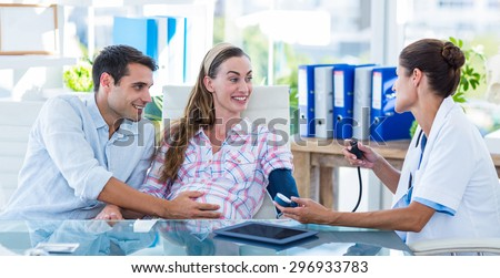 Doctor taking the blood pressure of a pregnant patient with her husband in an examination room - stock photo