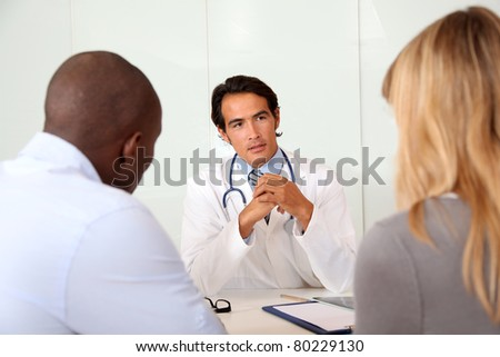 Doctor talking to couple in office - stock photo