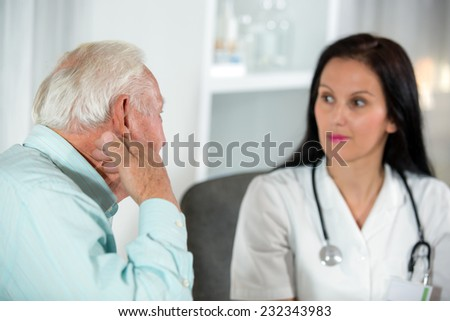 Doctor talking to her male senior patient at office - stock photo