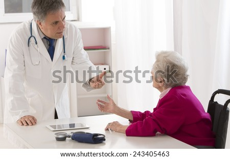 Doctor talking to his disabled senior patient at the office - stock photo