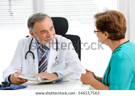 Doctor talking to his female senior patient at the office - stock photo