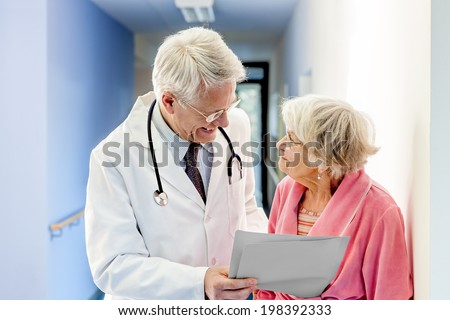 Doctor Talking to Old Woman about Good Results at the hospital. - stock photo