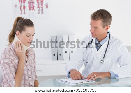 Doctor talking to patient wearing neck brace in medical office - stock photo