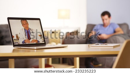 Doctor talking to patient who is texting on his smartphone - stock photo