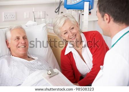 Doctor talking to senior couple on USA Hospital ward - stock photo