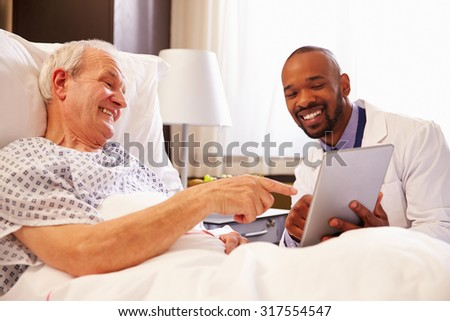 Doctor Talking To Senior Male Patient In Hospital Bed - stock photo