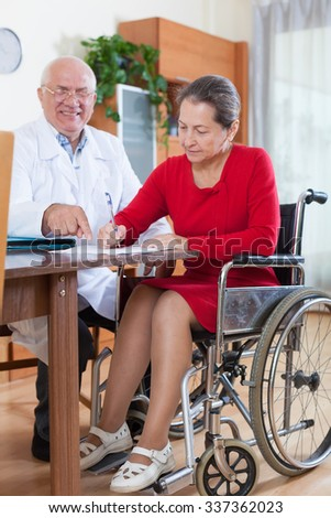 doctor talking to woman in wheelchair.     - stock photo