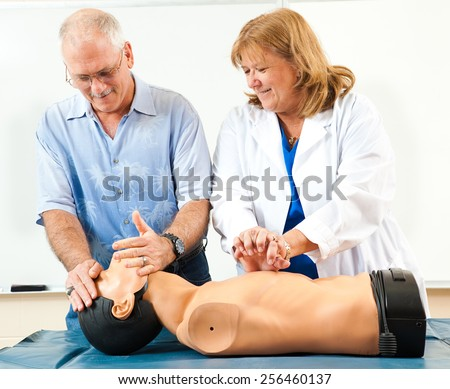 Doctor teaching CPR to a mature student.   - stock photo