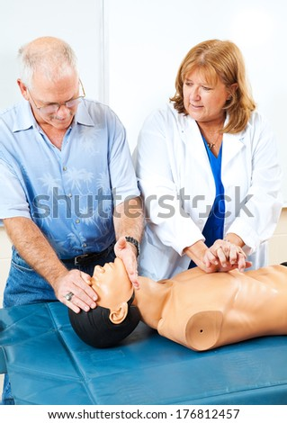 Doctor teaching first aid CPR to a mature adult student using a mannequin.   - stock photo