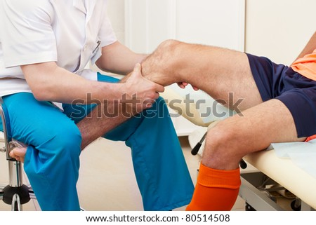 Doctor testing a knee for stability of injured football player in clinic - stock photo