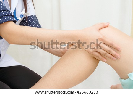 Doctor the traumatologist examines the patient's knee  - stock photo